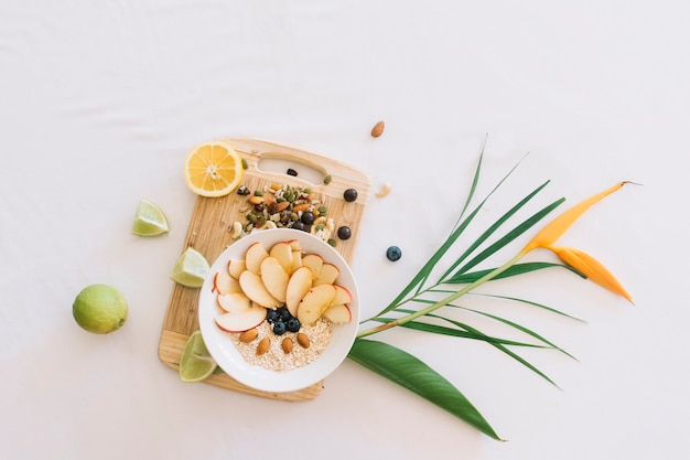 Harina de avena decorada con una rodaja de manzana y frutos secos en una tabla de cortar de madera