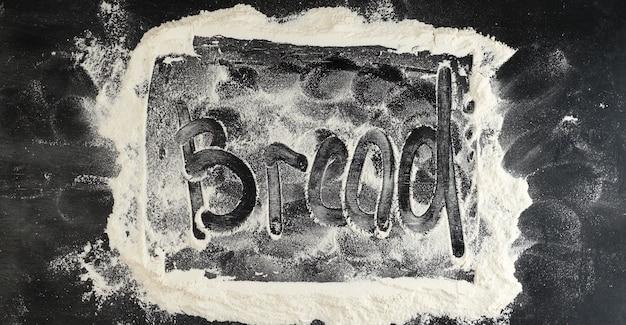 Harina blanca espolvoreada sobre una mesa negra e inscripción de pan en la superficie