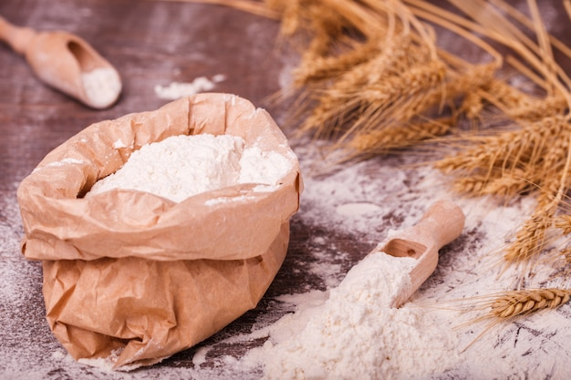 Harina en bolsa y cuchara de madera.