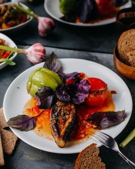 Harina de carne dolma con aceite de hojas moradas dentro de un plato blanco junto con panes de pan crujientes de verduras en gris