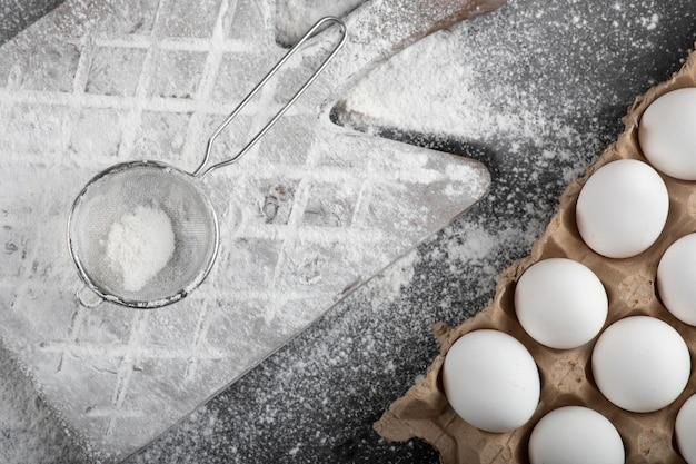 Harina derramada sobre tablero de madera y huevos crudos sobre superficie negra