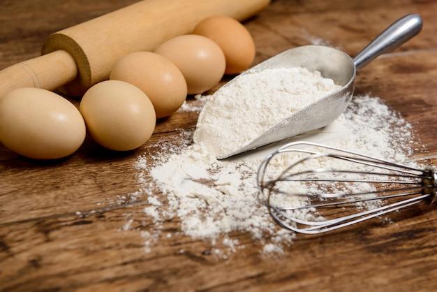 Harina, huevos y amasar sobre mesa de madera