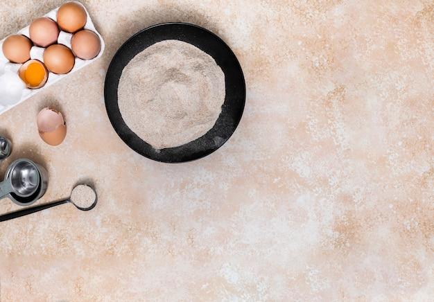 Harina; huevos en caja de cartón y cucharas de medir sobre fondo de textura beige
