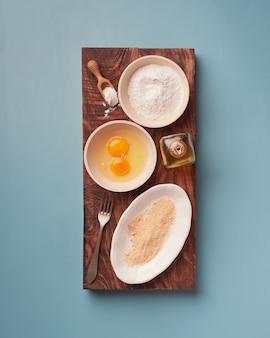 Harina, huevos y pan rallado, ingredientes para empanar colocados en platos y tazones sobre una tabla rectangular de madera oscura.