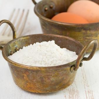 Harina y huevos en platos viejos.