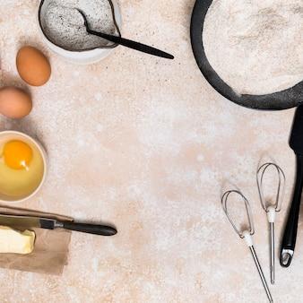Harina; huevos; yema de huevo; mantequilla y batidor en el mostrador de la cocina con espacio para escribir el texto