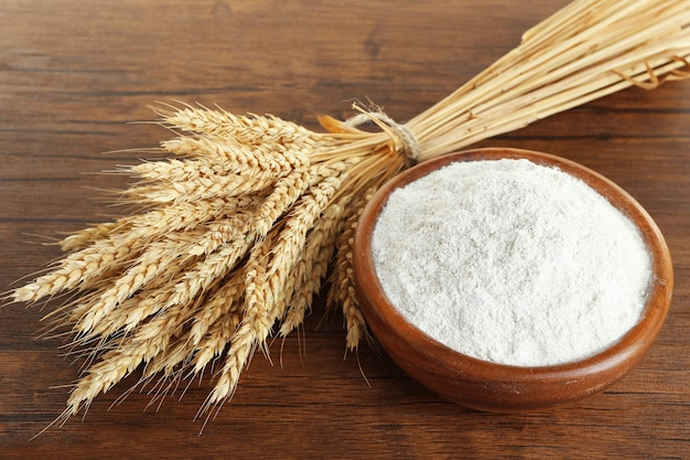 Harina integral en un tazón con espigas de trigo sobre la mesa de madera, primer plano