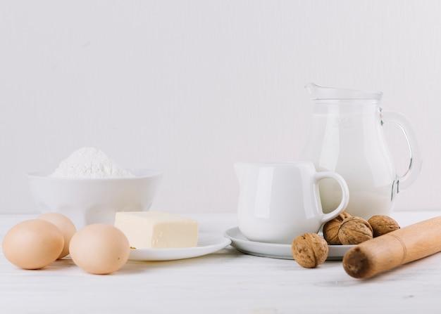 Harina; leche; huevos; queso; rodillo y nueces sobre fondo blanco para hacer pastel