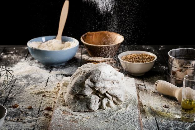 Harina que cae sobre la mesa de horno con ingredientes en el tazón