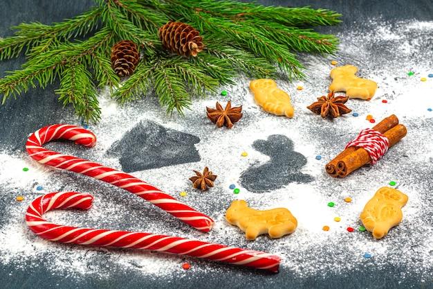 Harina silueta de galletas sobre fondo oscuro entre ramas de árboles de navidad, conos, anís estrellado, canela y bastón de caramelo.