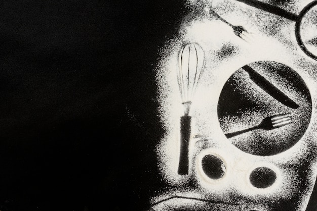 Harina sobre fondo negro con formas de elementos de cocina