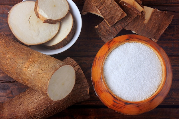 Harina de tapioca en un tazón de madera sobre una mesa rústica de madera, junto a la yuca cortada y en rodajas