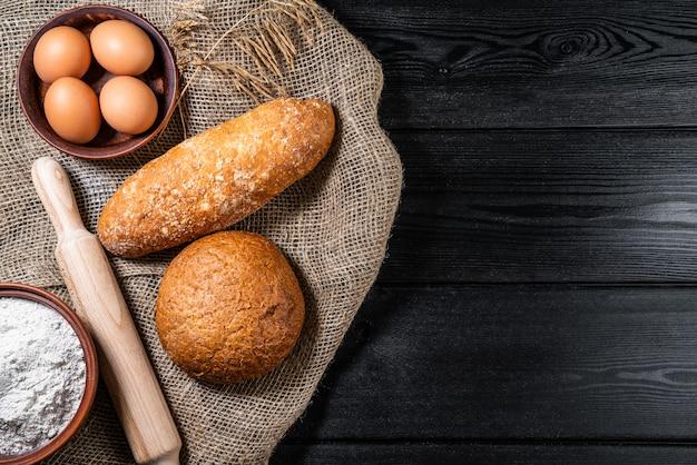 Harina en un tazón de madera sobre una mesa de madera oscura con espiguillas de trigo, huevos