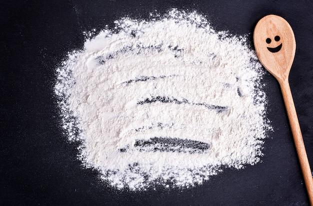 Harina de trigo blanca dispersa sobre un fondo negro
