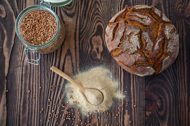 Harina de trigo sarraceno, granos de trigo sarraceno y pan sobre una superficie de madera