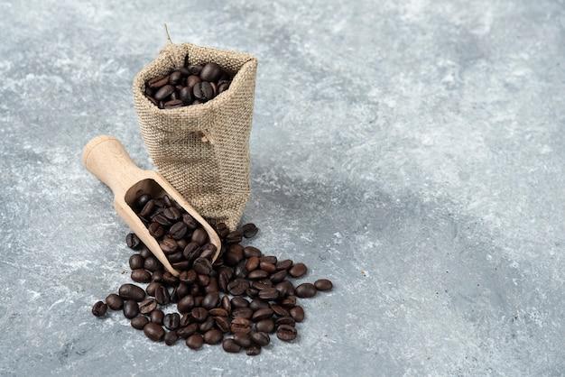 Harpillera llena de granos de café tostados y cuchara de madera sobre superficie de mármol.