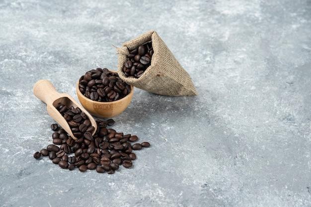 Harpillera llena de granos de café tostados y cuenco de madera sobre superficie de mármol.