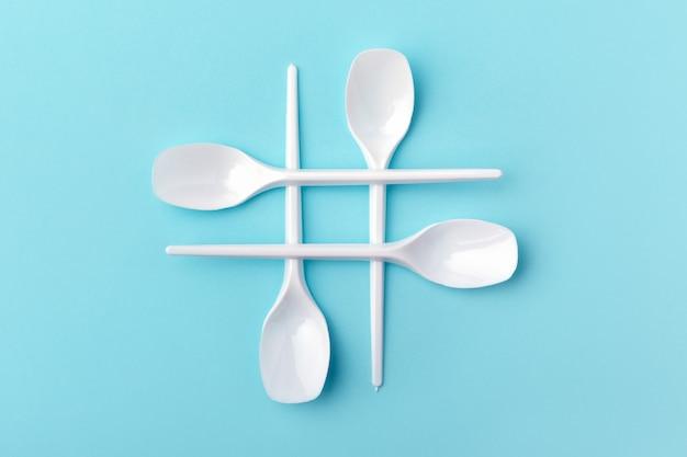 Hashtag hecho de cucharas de plástico blanco sobre fondo azul. concepto de problema ecológico.