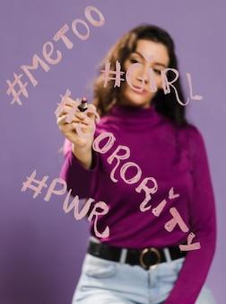 Hashtags palabras escritas en un cristal transparente por mujer