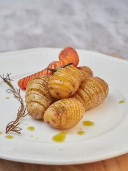 Hasselback de patata y zanahoria asada en un plato blanco, vista cercana espacio borroso