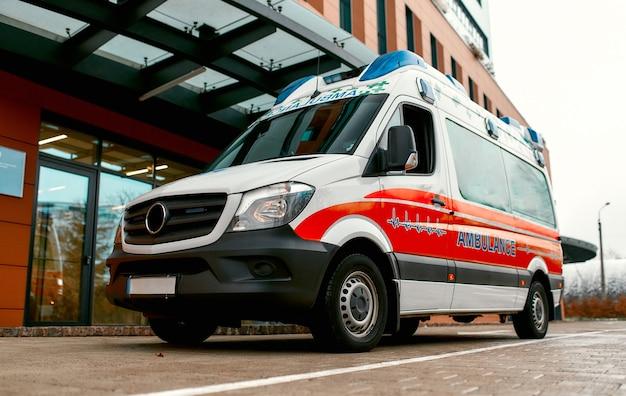 Hay una ambulancia frente a un hospital moderno. médico a domicilio, concepto de atención médica.