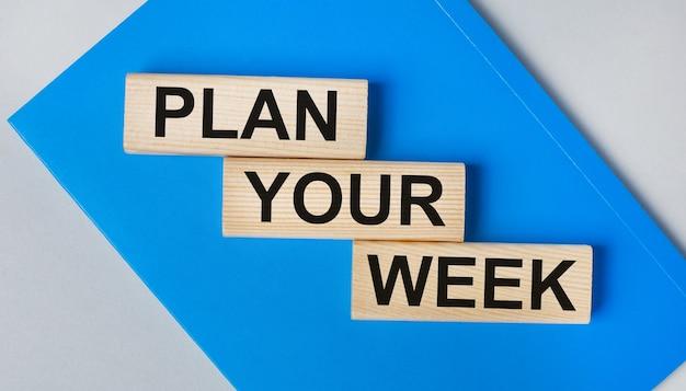 Hay un cuaderno azul sobre un fondo gris claro. arriba hay tres bloques de madera con las palabras planifique su semana.