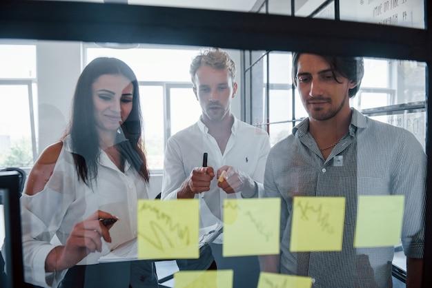 Hay pegatinas amarillas en el cristal. jóvenes empresarios en ropa formal que trabajan en la oficina.