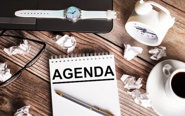 Hay una taza de café en una mesa de madera, un reloj, vasos y un cuaderno con la palabra agenda