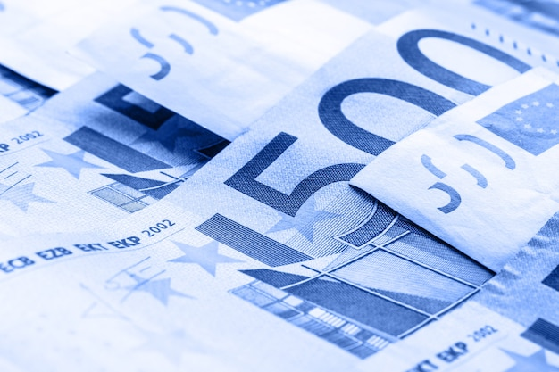 Hay varios billetes y monedas de 500 euros adyacentes. foto simbólica de la riqueza. equilibrio de monedas de euro en la pila con el fondo de los billetes.