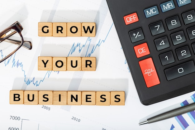 Haz crecer tu concepto de negocio. bloques de madera con frase, calculadora y caracteres impresos.