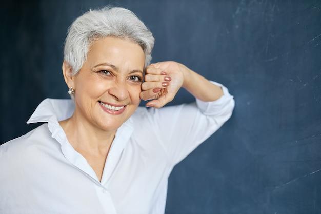 Headportrait de feliz hermosa mujer madura experta en marketing con elegante corte de pelo corto que descansa durante el descanso mientras trabaja en la oficina