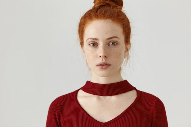 Headshot de moda hermosa joven jengibre mujer caucásica con moño y pecas. concepto de diseño de moda y ropa