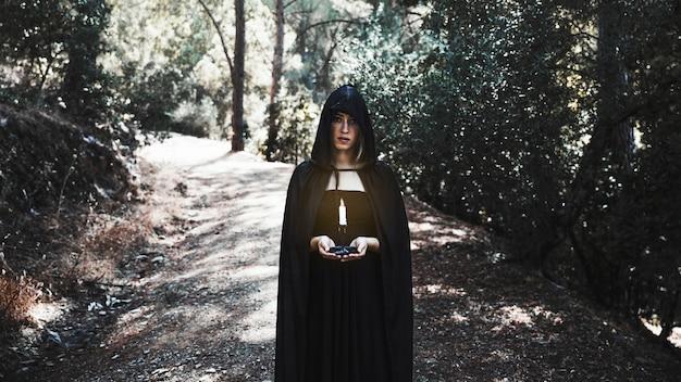 Hechicera en cabo con vela en el bosque soleado