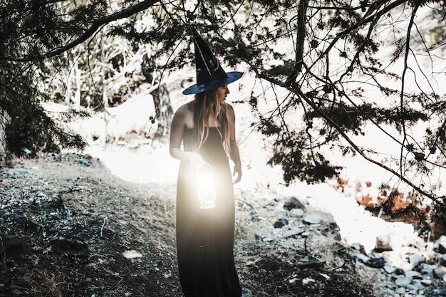 Hechicera con linterna en el matorral durante el día