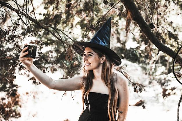 Hechicera sonriente usando el teléfono para selfie en el bosque soleado