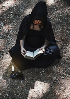 Hechicero femenino que sostiene el libro abierto y que se sienta en la tierra del bosque