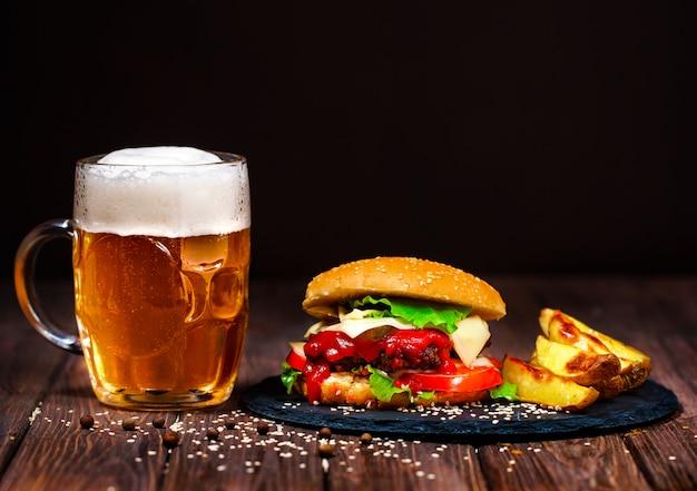 Hecho en casa, deliciosa hamburguesa de ternera con lechuga y patata, un vaso de cerveza servido sobre una tabla para cortar piedra. oscuro
