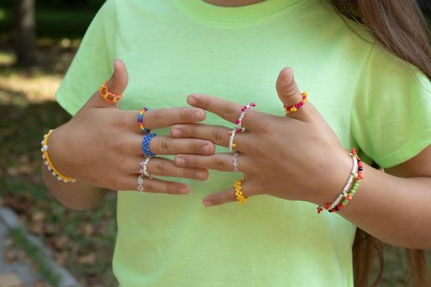 Hecho a sí mismo - anillos y pulseras - adornos de cuentas en las manos de la niña.