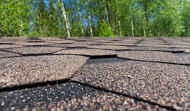 Hecho de tejas flexibles bituminosas en el techo de un edificio