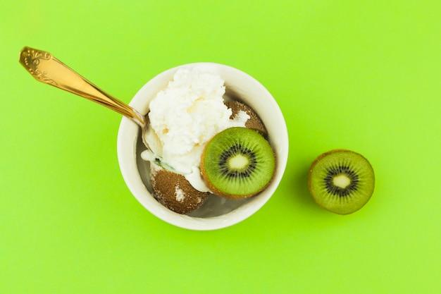 Helado cerca de cuchara y kiwi en un tazón