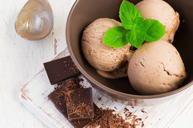 Helado de chocolate con hoja de menta en un tazón marrón
