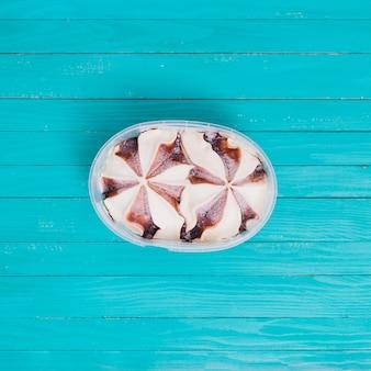 Helado con chocolate en un recipiente de plástico sobre superficie de madera