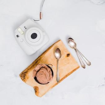 Helado de chocolate en soporte de madera con cucharas y cámara desechable.