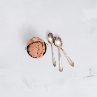 Helado de chocolate en un tazón con cucharas en la superficie de mármol