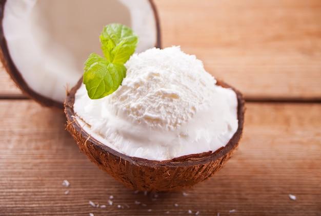 Helado de coco en la mesa de madera con hoja de menta