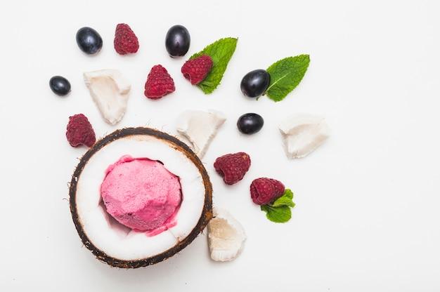 Helado congelado en el interior del coco con frambuesa; menta y uvas sobre fondo blanco