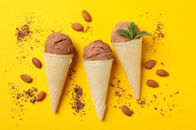 Helado en conos y almendras en superficie amarilla. comida dulce