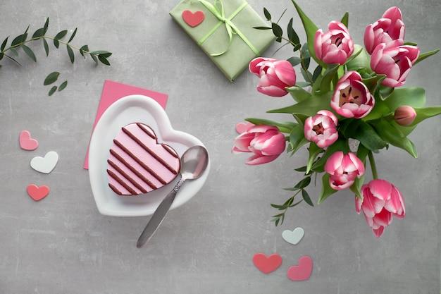 Helado de corazón rosa en plato de cerámica y ramo de tulipanes rosados