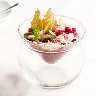 Helado crudo rosado de la crema batida del postre con las bayas y las nueces en el tarro de cristal en la tabla blanca
