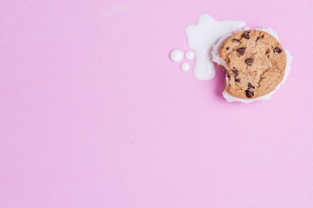 Helado derretido y galleta sobre fondo rosa espacio de copia